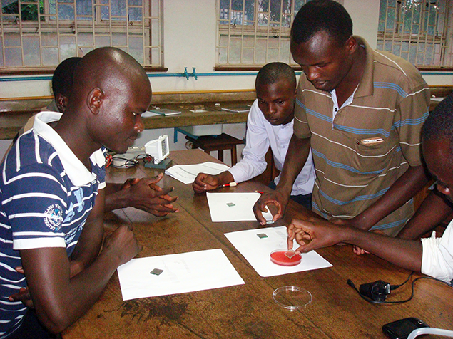 Students in Africa work with an experiment kit from SciBridge.