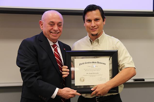 Dr. Joseph DeCarolis, right, accepts his Alcoa award from Dr. Louis A. Martin-Vega.