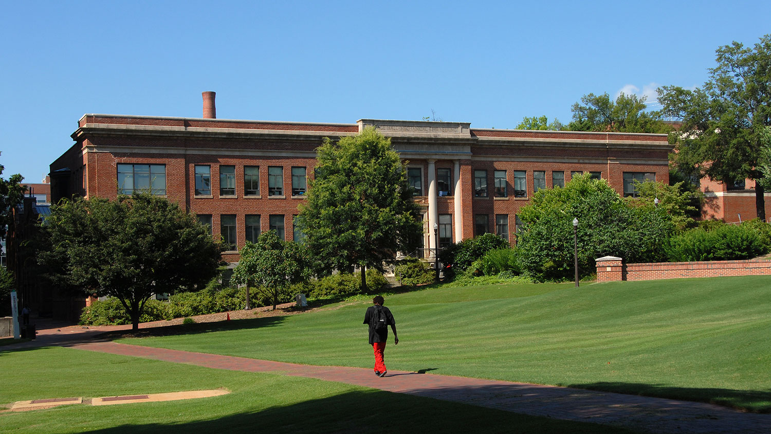 Student heads across Court of North Carolina towards Page Hall.