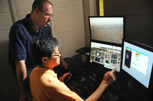 Dave Kaber looks over a graduate student's shoulder as they test flight simulator in Daniels Hall.