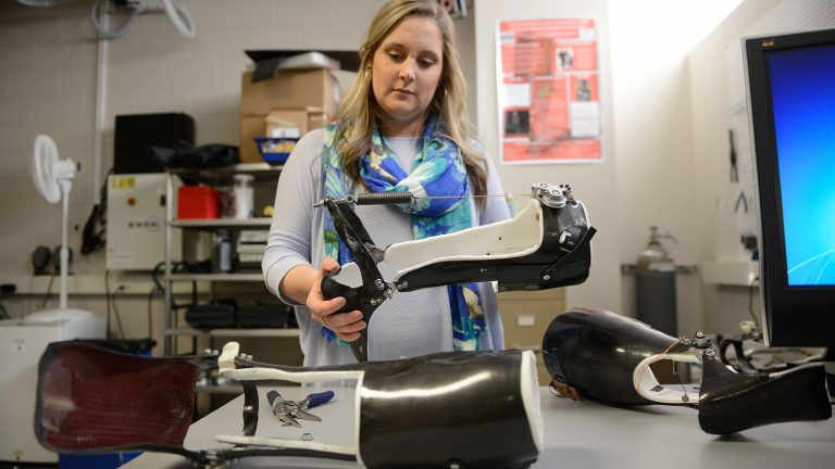 Student examines a rehabilitation device in the Power (GAIT) Lab in EB III.