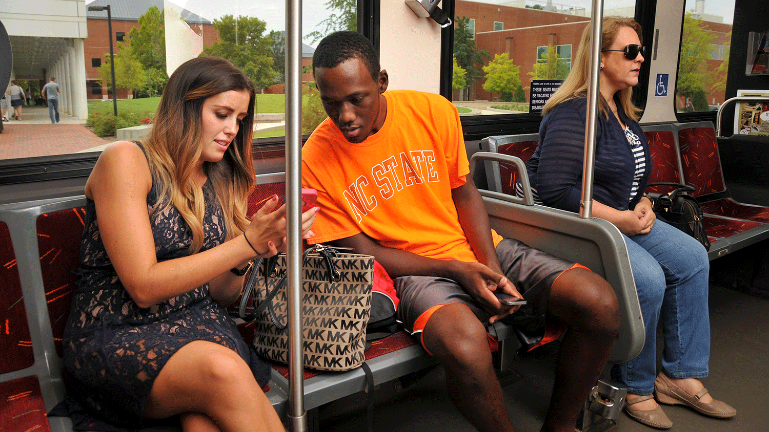 Wolfline bus riders chat while crossing through Centennial Campus.