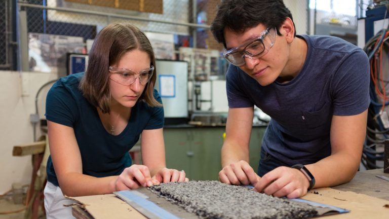 Dr. Cassie Castorena and Ph.D. student Kangjin Lee examine a chip seal used for pavement preservation.