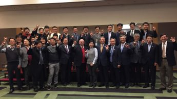 Participants in College of Engineering's first alumni event held in South Korea show wolf hands.