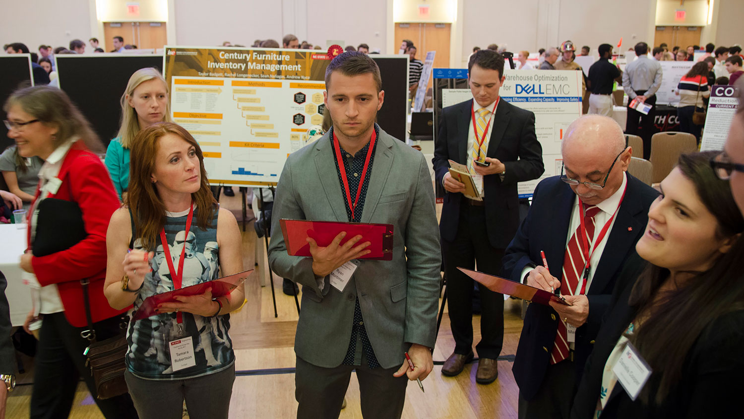 From left, engineering design day judges Tamara Robertson, NC State alumna ('09) and finalist on Mythbusters: The Search; Dr. Louis Martin-Vega, dean of the College; and Ryan Mortimer speak with students as the present their senior design project. (Photo: Robert Lasson, 2017)