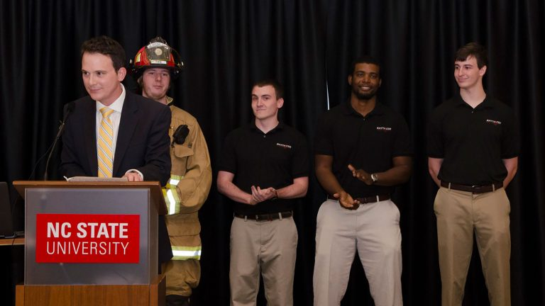 Host of the award ceremony, WRAL's Brian Schrader, speaks about the winning team of design day, PulseAware, a firefighter heart monitor. (Photo: Robert Lasson, 2017)