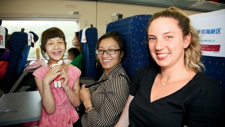 Engineering student interacts with train passengers in China.