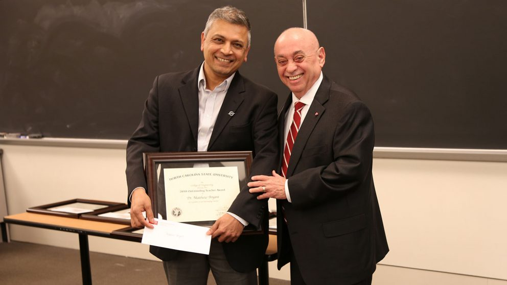 MAE department head Dr. Srinath Ekkad accepts the award from Dean Louis Martin-Vega on Bryant's behalf.
