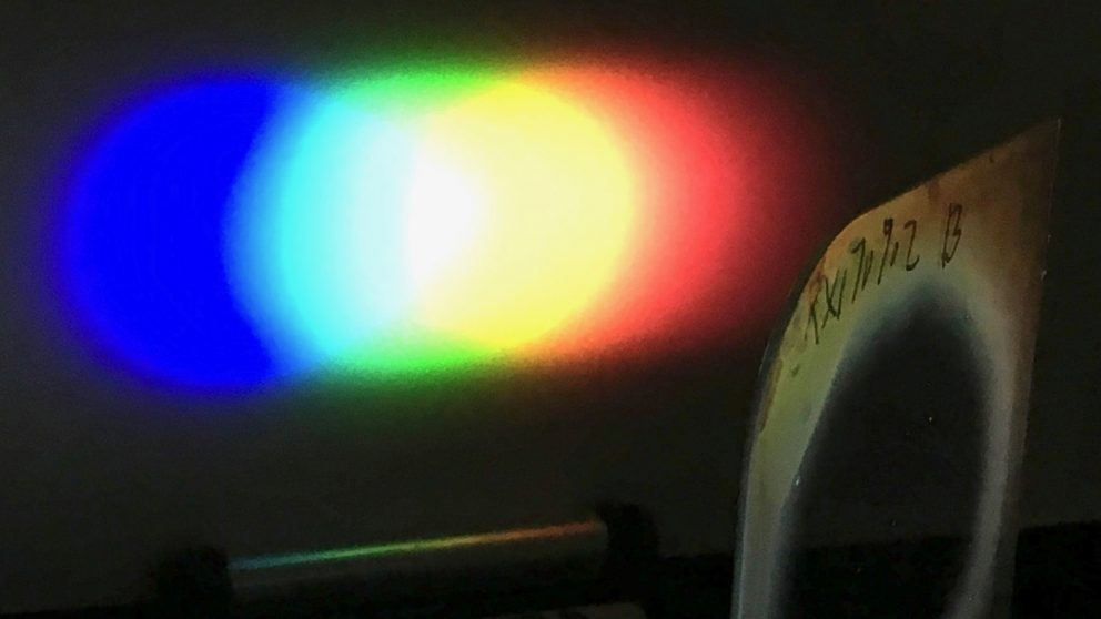 A one-inch diameter Bragg polarization grating diffracts white light from an LED flashlight onto a screen placed nearby.