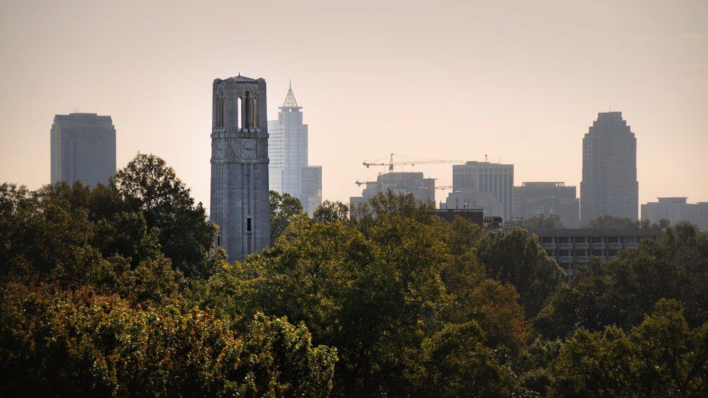 Downtown Raleigh skyline rises up behind the Memorial Belltower.