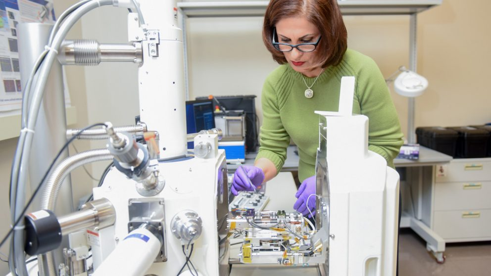 Afsaneh Rabiei is pictured here with the device she developed that can capture scanning electron microscopy (SEM) images in real time at temperatures up to 1,000 degrees Celsius while applying stresses as high as two gigapascal.