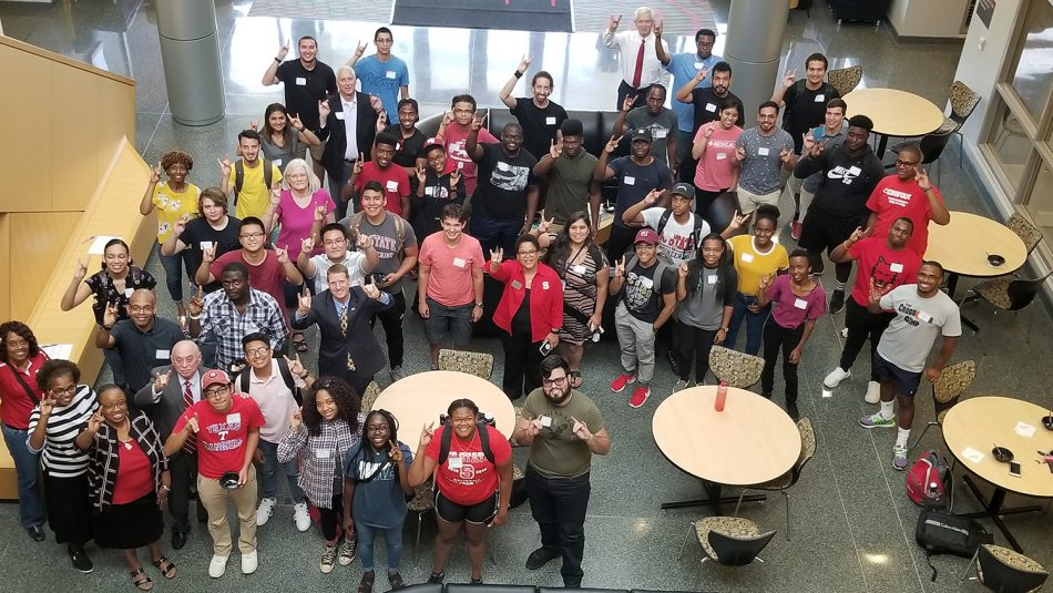 Students, faculty and staff raise wolf hands at ice cream social sponsored by the College of Engineering Minority Engineering Programs and Graduate programs.