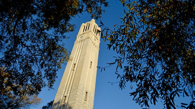 Early morning sun cuts across the Memorial Belltower and Fall colors.