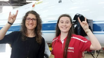 Christina Koch and Madison Maloney in front of NASA shuttle.