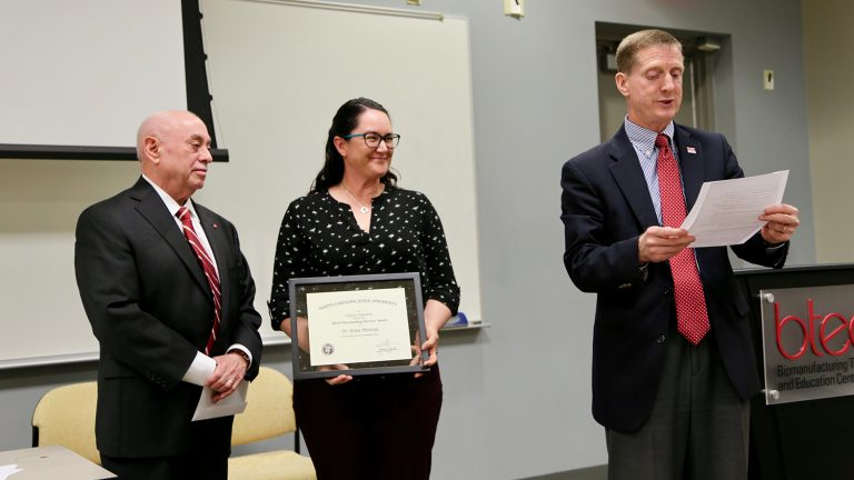 Dr. Brina Montoya, center, accepts an Outstanding Teacher Award from Dr. Louis Martin-Vega while Dr. Jerome Lavelle reads her citation.