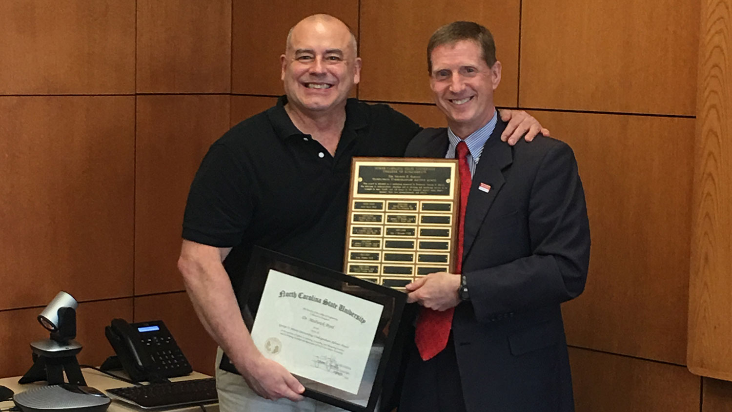 Dr. Jerome Lavelle, right, presents the George H. Blessis Outstanding Undergraduate Advisor Award to Dr. Medwick Byrd.