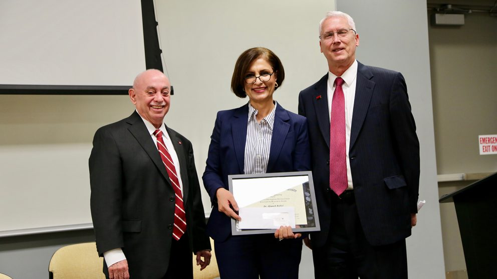 Dr. Afsaneh Rabiei, center, accepts Alcoa Foundation Distinguished Engineering Research Award from Dr. Louis Martin-Vega, left, and Dr. John Gilligan.
