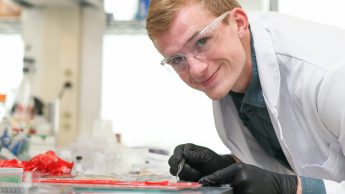 Neil Baugh leaning over his lab bench, smiling at the camera.