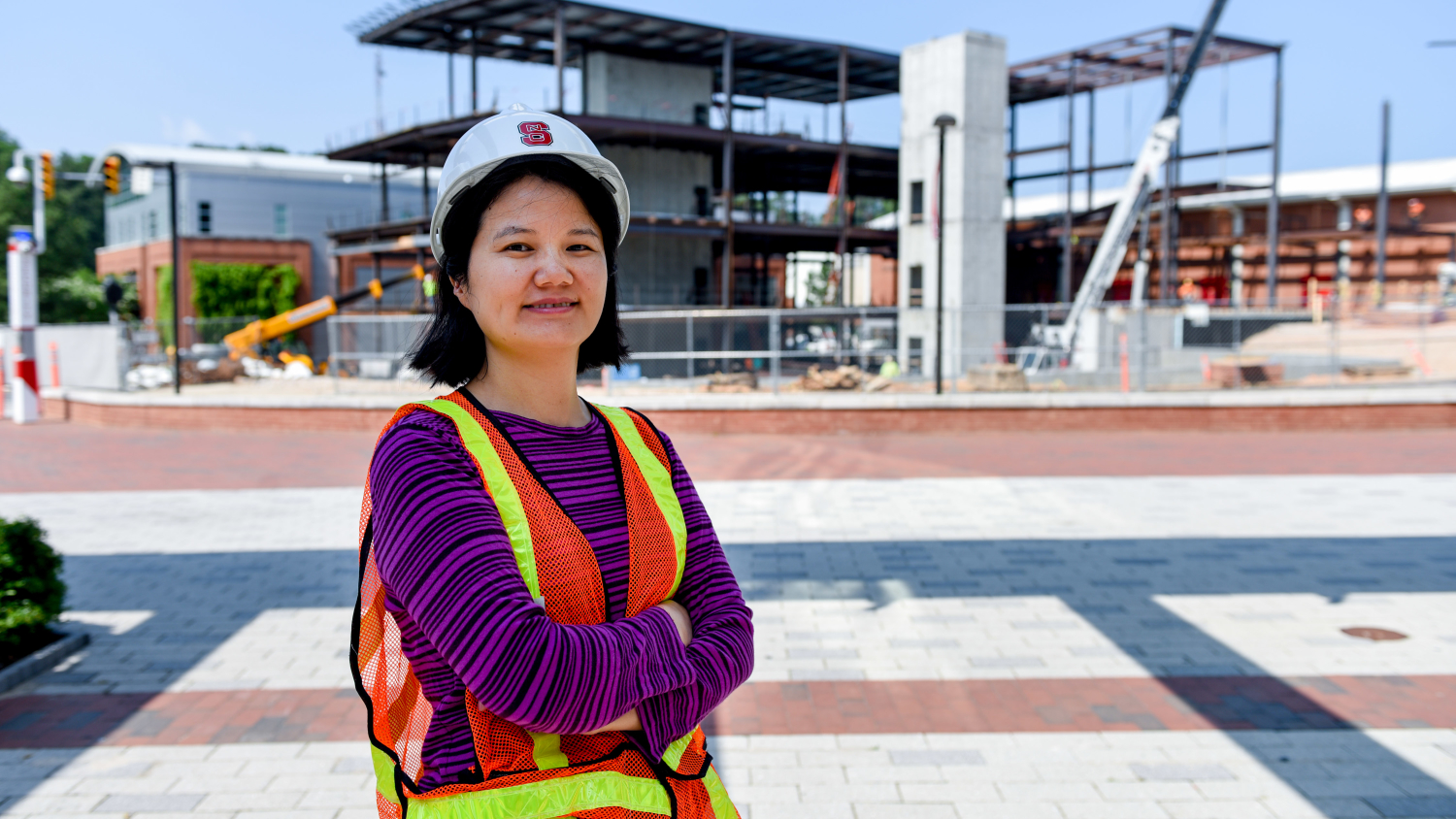 Dr. Min Liu stands in front of Wellness and Rec Center construction