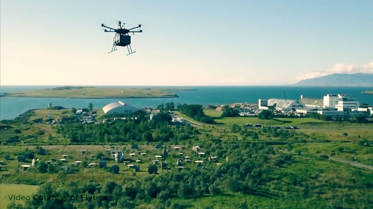 A drone flies over the skyline with a package