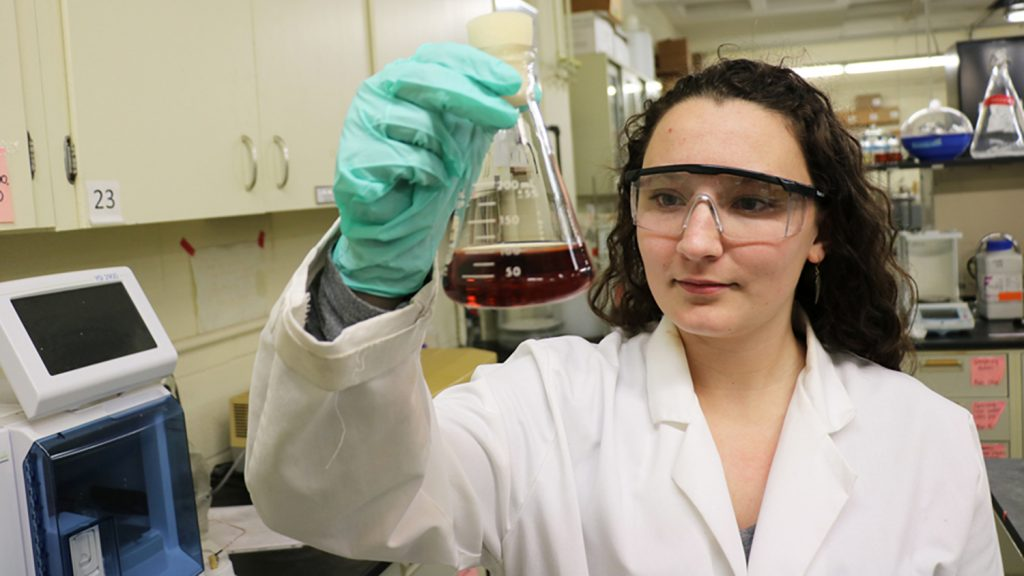 Erin Cooper examines flask in lab.