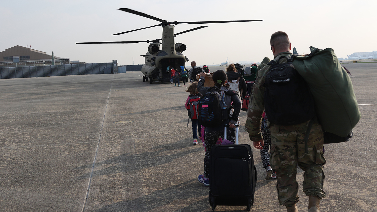noncombatants boarding a military transport helicopter