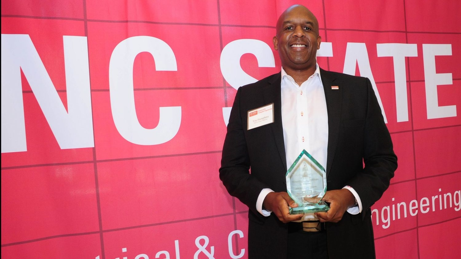 Tim Humphrey holding his Hall of Fame statuette in front of red background