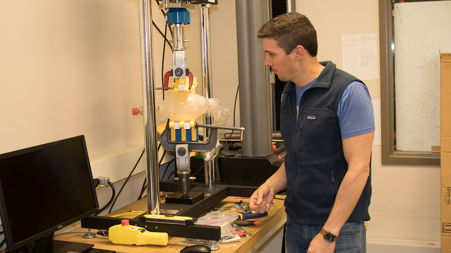 Landon Grace, an assistant professor of mechanical and aerospace engineering at NC State University, works with the emergency ventilator prototype (Photo by NC State University)