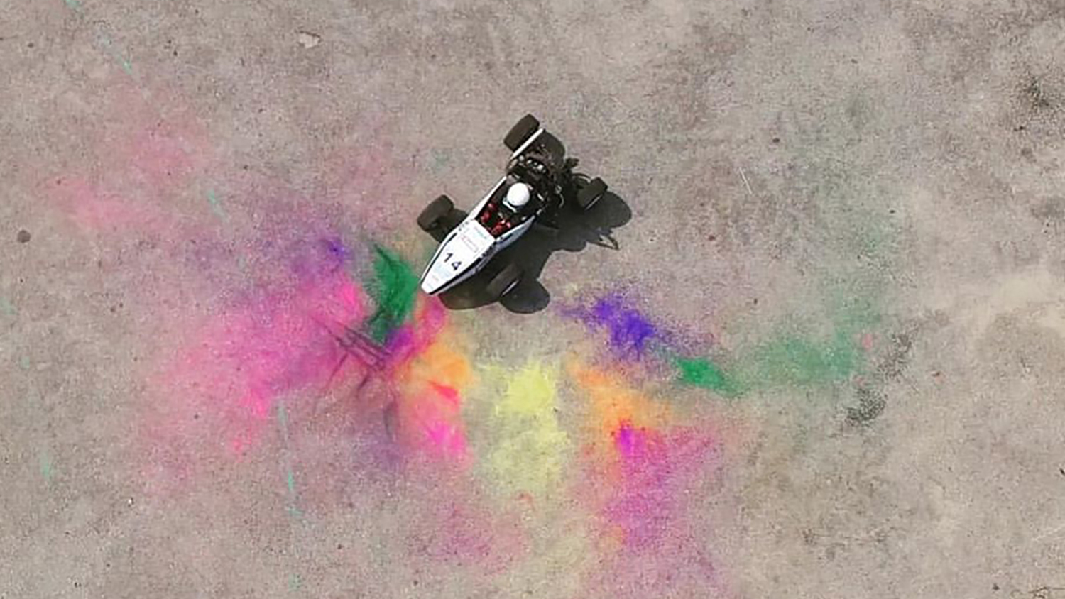 """The photo """"testing + holi"""" shows an engineering project centered in colorful powder."""