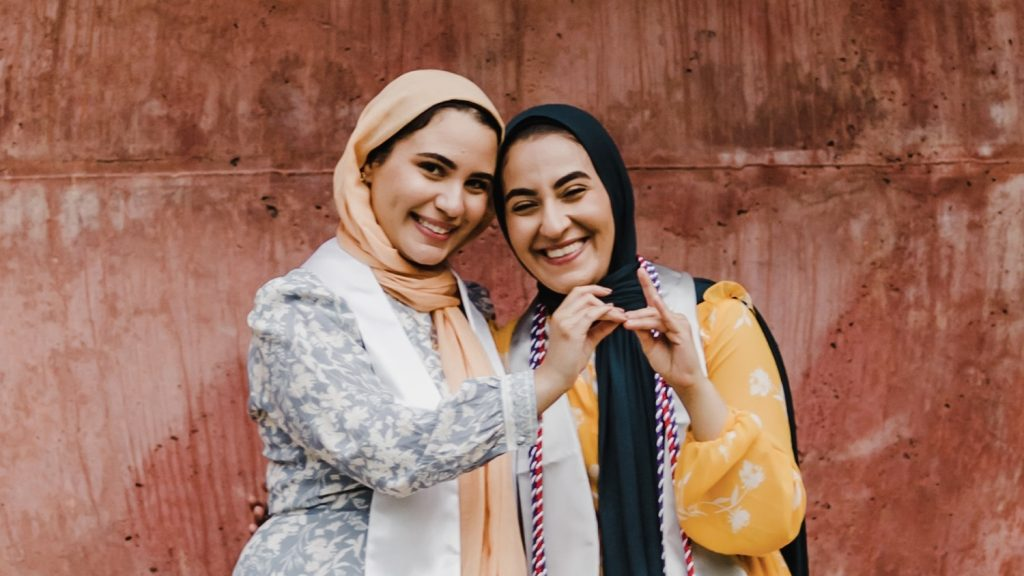 Twin sisters Iman, left, and Salam pose together at a Wolf Ears sculpture on campus and make wolf hands gestures.