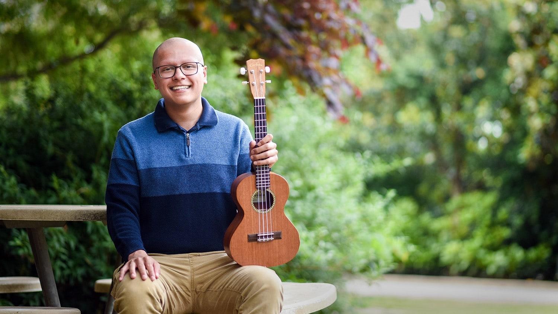 Nikhil Milind sitting outside, holding his ukulele.