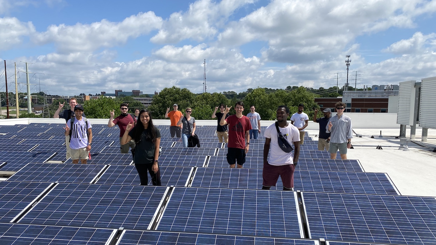 Group of students standing among rows of solar panels.