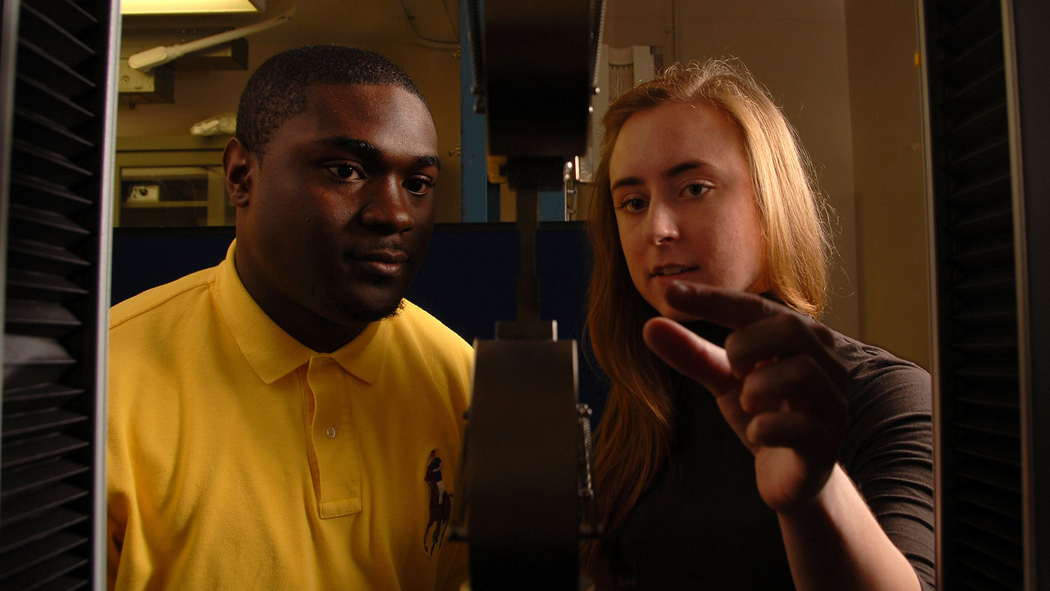 Two nuclear engineering students check on structural stability of a sample.