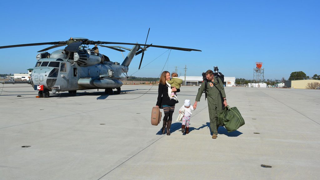 Soldier meets wife and two children on the tarmac.